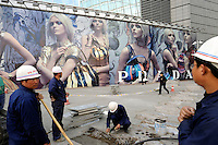 Chinese workers pave tiles in front of a huge Prada billboard at Shin Kong Place, which is one of the most luxurious shopping centers in Beijing, having successfully attracted 938 international class brands, they also boast the largest Gucci flagship store in Asia..