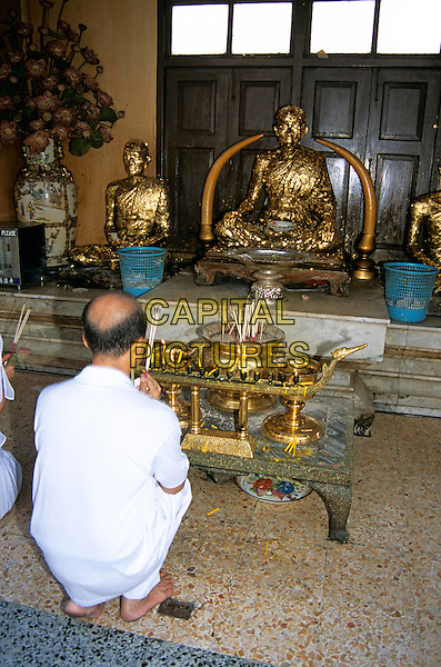 Worshipper praying, Temple of the Golden Buddha, Wat Traimit (also known as Wat Trimitr), Bangkok, Thailand