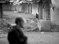 A Palestinian boy looks at Israeli soldiers during a curfew in Hebron, West Bank.