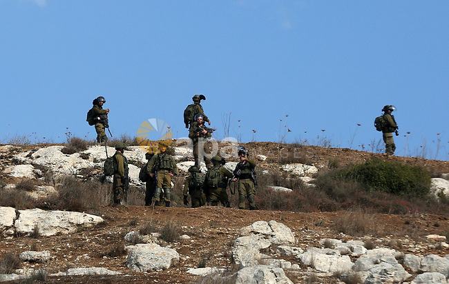 Israeli security forces take position during clashes with Palestinian protesters following a weekly demonstration against the expropriation of Palestinian land by Israel in the village of Kfar Qaddum, near the West Bank city of Nablus on December 6, 2019. Photo by Shadi Jarar'ah