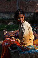 Meera sits in the sun in the compound where she lives in with her family in Varanasi, Uttar Pradesh, India on 19 November 2013.