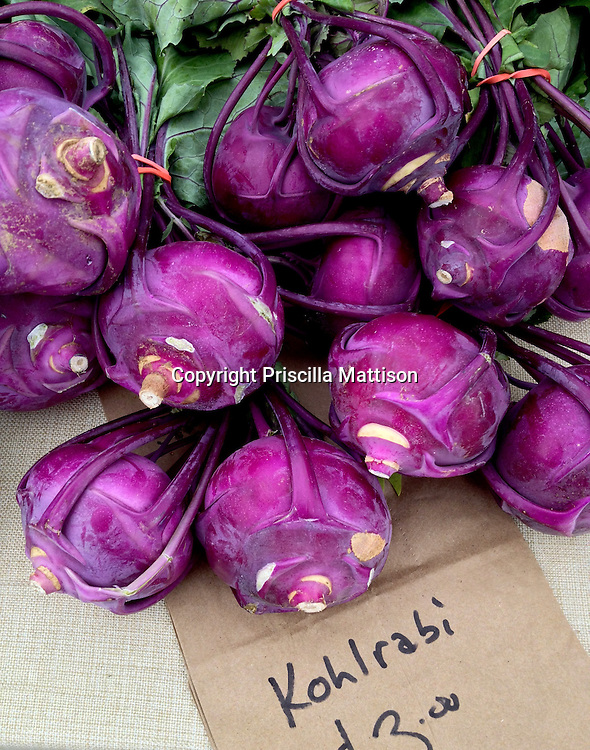 Bunches of purple kohlrabi are laid out for sale.