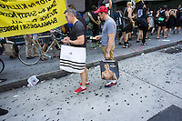 Shoppers observe hundreds of workers and supporters as they march through the streets of Soho on Saturday, June 29, 2013 stopping off at various clothing retailers protesting the companies' refusal to the Bangladesh Safety Accord guaranteeing better safety conditions in Bangladeshi factories. In April a collapse of an enormous garment factory killed over 1000 workers. (© Richard B. Levine)