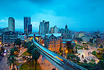 The elevated Medellin Metro is in motion as it leaves Parque Berrio Station in front of Plaza Botero.  The domed illuminated Palace of Culture stands among the modern buildings of downtown at dawn.