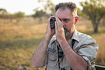 Cheetah (Acinonyx jubatus) biologist, Luke Hunter, observing herbivores during transect, Kafue National Park, Zambia