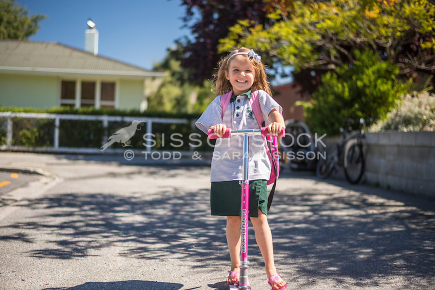 Primary school girl in uniform smiling and scootering home from school on a summers day, New Zealand - stock photo, canvas, fine art print