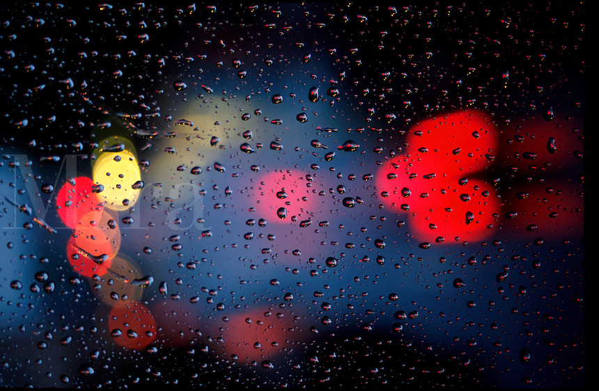Abstract view of raindrops on a window with neon lights in the background.