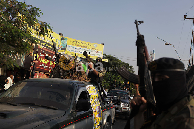 Members of the Palestinian Islamic Jihad movement parade with guns on November 13, 2013 in the streets of Gaza City during an anti-Israel march as part of the celebrations marking the first anniversary of Israel's Operation Pillar of Defence. Photo by Ashraf Amra