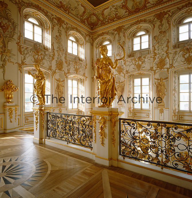 The State Staircase at Peterhof is decorated with gilded statues and urns of fruit and the walls are painted with extravagant murals
