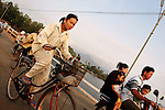 CAMBODIA  -  APRIL 3, 2005:  A woman riding a bicycle and mopeds carrying multiple people cross the Kampot River on a bridge on April, 3, 2005 in Kampot, Cambodia, (PHOTOGRAPH BY MICHAEL NAGLE).