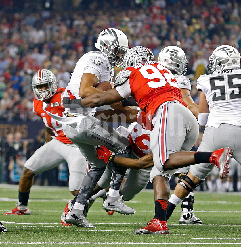 Ohio State Buckeyes linebacker Darron Lee (43) and Ohio State Buckeyes defensive lineman Adolphus Washington (92) sack Oregon Ducks quarterback Marcus Mariota (8) during the 2nd quarter in College Football Playoff Championship game at AT&T Stadium in Arlington, Texas on January 12, 2015.  (Dispatch photo by Kyle Robertson)