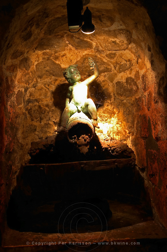 A statue on a piedestal in the underground cellar at Guigal showing a small Bacchus or naked cherub sitting on a wine barrel holding a grape bunch in his hand.  Domaine E Guigal, Ampuis, Cote Rotie, Rhone, France, Europe