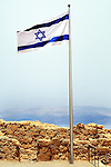 Israeli flag blowing in the breeze above Masada