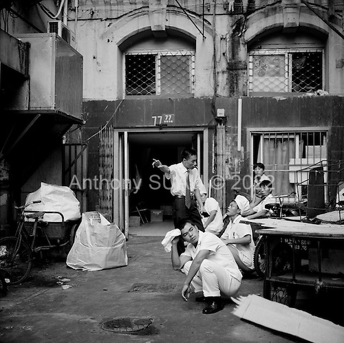 Shanghai, China.July 16, 2006..Employees sit in the heat behind restaurant.