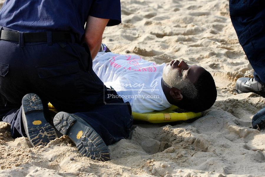 EMTs helping an African American teenager hurt on a beach