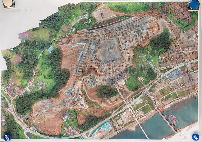 Photo shows an aerial view of the rebuilding project in Rikuzentakata, Iwate Prefecture, Japan. Atlas Copco drill rigs are a key feature of the project, which will shift blasted rubble from a nearby hillside to the central part of the city, which was flattened by the 2011 tsunami, where the land will be raised 10 meters.. Rob Gilhooly Photo