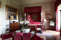 A four-poster bed hung with crimson damsk drapes with an embroidered coat of arms and heraldry