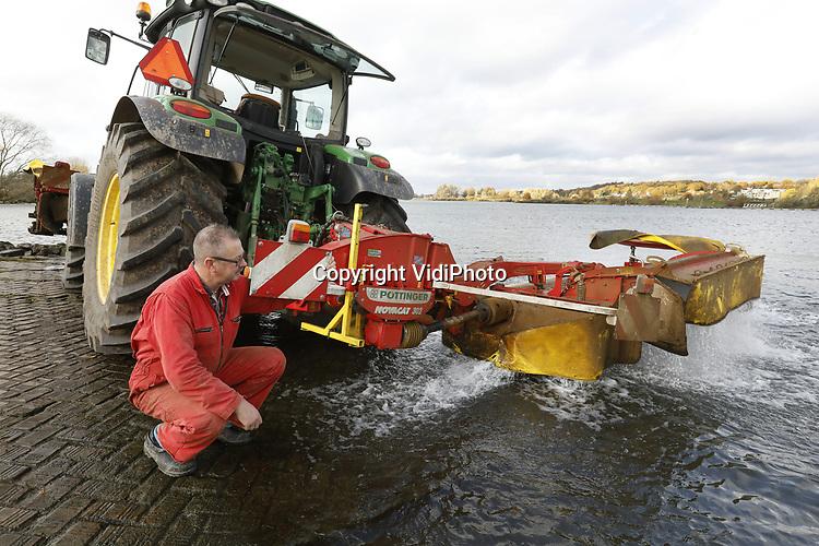 Foto: VidiPhoto<br /> <br /> LIENDEN &ndash; Loonwerker Hans van Kalkeren uit Lienden in de Betuwe spoelt dinsdag zijn maaier/kneuzer in de Rijn bij Lienden. Enkele weken geleden is het laatste gras gemaaid. De resten zitten vastgekoekt aan de machines en om dat los te weken rijdt Van Kalkeren zijn tractor half in de Rijn en laat hij de snijmessen draaien in het water om de grasresten los te weken. Tien minuten spoelen in de Rijn bespaart hem anderhalf uur werk thuis op het bedrijf. Overigens krijg het mechaniek daar nog een nabehandeling met een hogedrukspuit, voordat het voor een half jaar de &lsquo;kast&rsquo; in gaat.