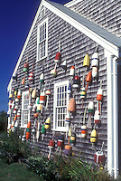AJ1493, Cape Cod, Massachusetts, Colorful fishing buoys hanging from the side of a house in North Truro, Massachusetts.