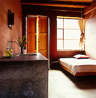 This minimal guesthouse bedroom is furnished with a concrete washbasin