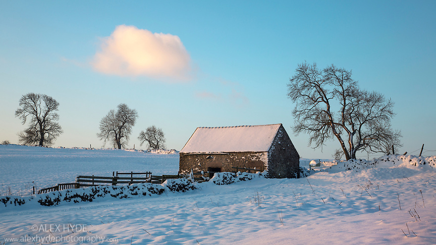 Stone field barn at dawn following heavy snowfall. Peak DIstrict National Park, Derbyshrie, UK. December.