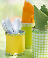Tin cans covered in colourful fabric make simple and pretty pots for napkins and cutlery at a children's party