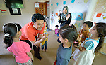 Emad Almoqari leads a group of children in an activity at the Youth Empowerment Center in Beit Hanoun, Gaza, as Shoroug Faraj Allah looks on. The program is supported by Caritas and DanChurchAid, a member of the ACT Alliance, and is designed to help children better cope with the trauma they experienced during the 2014 war.<br />