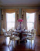 Upholstered dining chairs surround an elegant laid table in this London dining room