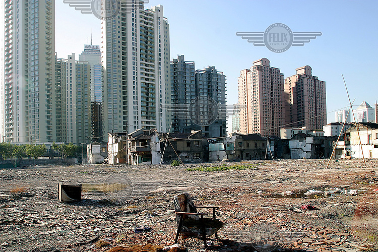 An abandoned sofa sits on the site of recently demolished housing. Issues concerning the rights of relocated residents have been brought into the spotlight with the arrest of real estate tycoon Zhou Zhengyi and the self-immolation of several disgruntled residents from around the country. The plot of land shown here is controlled by Mr. Zhou, located on the corner of Beijing Road and Chengdu Road.