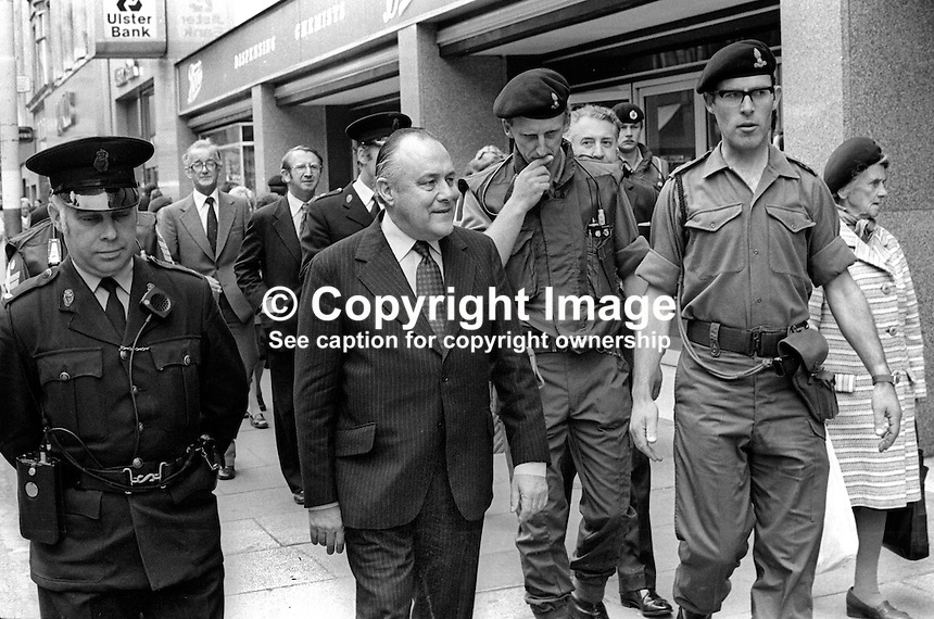 New Zealand Prime Minister, Sir Robert Muldoon, flanked by police and soldiers, in the main shopping area of Belfast during a one-day visit to the city on 20th June 1975. 197506200079a<br />