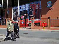 May 4th 2020, Liverpool, United Kingdom;  Anfield stadium during the suspension of the Premier League due to the coronavirus pandemic ;  a man wearing a face mask walks past the deserted entrance to the Kop