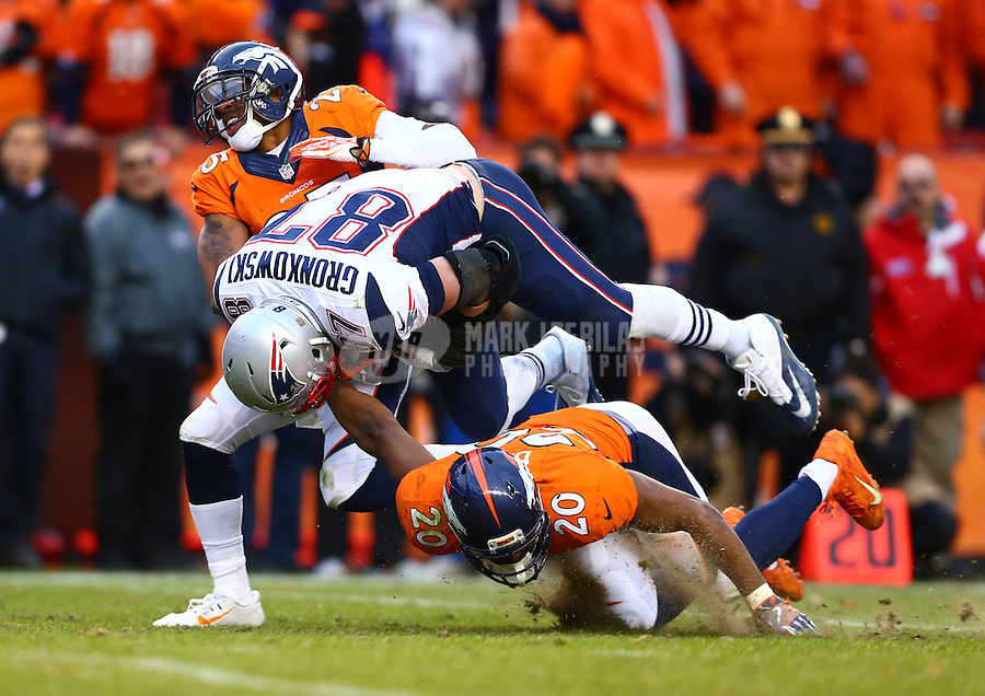 Jan 24, 2016; Denver, CO, USA; New England Patriots tight end Rob Gronkowski (87) is tackled by Denver Broncos safety Josh Bush (20) and cornerback Chris Harris Jr. (25) in the AFC Championship football game at Sports Authority Field at Mile High. Mandatory Credit: Mark J. Rebilas-USA TODAY Sports