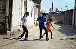 Three Roma children play football (soccer) in Suto Orizari, the Macedonian municipality that is Europe's largest Roma settlement.