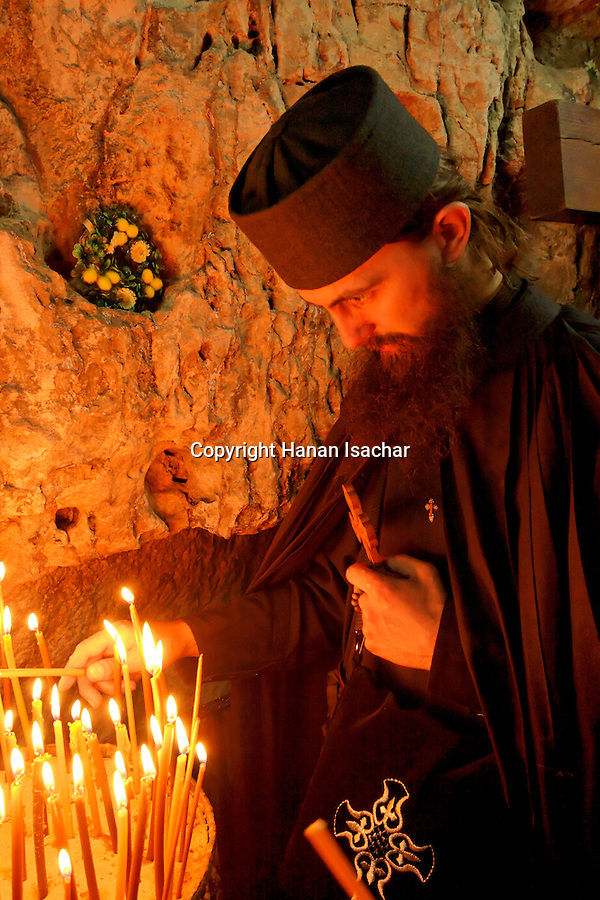 Israel, Jerusalem Old City, a Monk lights candles on Good Friday at the prison of Christ by the Via Dolorosa,  Easter 2005<br />