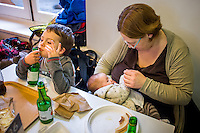 A mother breastfeeding her baby in a museum cafe while her older son drinks juice from a bottle with a straw.<br /> <br /> London, England, UK<br /> 08/03/2015<br /> <br /> &copy; Paul Carter / wdiip.co.uk
