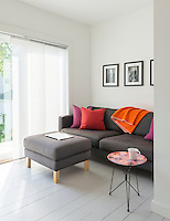 A corner of a white sitting room with a picture window dressed with a vertical, overlapping blind. The room is furnished with a sofa and ottoman upholstered in grey with a contrast provided by some bold pink and purple cushions. The white painted floorboards give the room a Scandinavian feel.