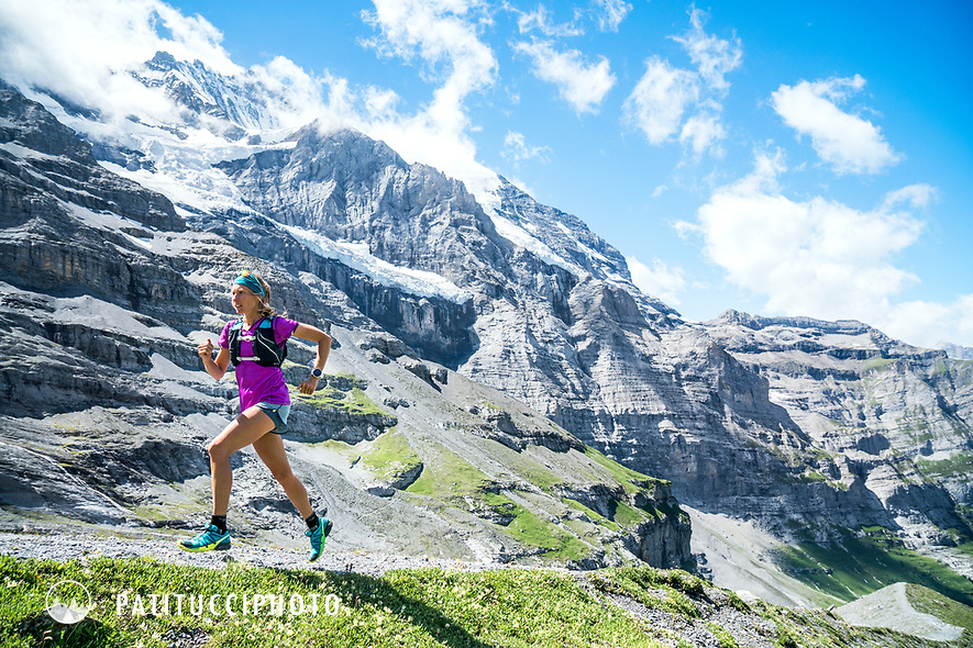 A woman trail running in the Jungfrau Region of Switzerland with the Jungfrau above.