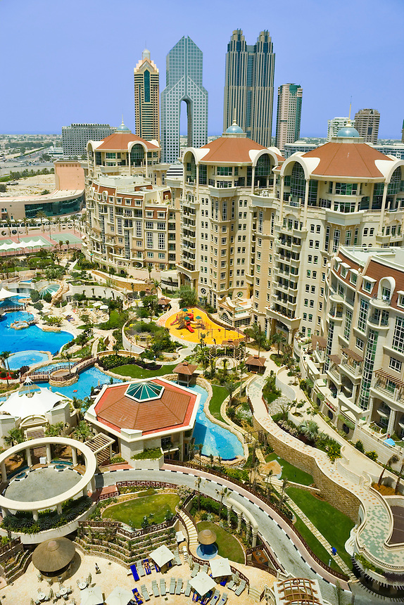Al Murooj Rotana Hotel and apartments, pool and recreation area, tall buildings on Sheikh Zayed Road in the background.  Dubai. United Arab Emirates.