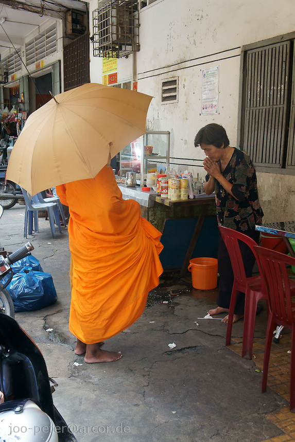 woman receives blessings by monk after donating, Phnom Penh, Cambodia, August 2011