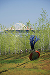 """Typewriter Eraser, Scale X"" by Claes Oldenburg and Coosje van Bruggen sits in the West Meadow section of Seattle's new Olympic Sculpture Park.  Seen from the north looking south, the sculpture is backed by a maturing forest of native aspen trees in the Grove, the towering orange cranes of the Port of Seattle abuot 3-1/2 miles away, and snow-capped Mt. Rainier some 60 miles distant.   SAM's Olympic Sculpture Park, Seattle, WA."