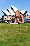 A young woman writes postcards at Dawes Point Reserve on Sydney harbour.  Sydney, New South Wales, AUSTRALIA