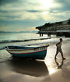 BRAZIL, Rio de Janiero, a fishermen preparing to push his boat into the water at Copacabana Beach
