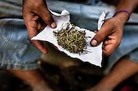 A young Guatemalan boy shows a package of natural marijuana grown outdoors on the Guatemala-Mexico border in Tecun Uman, Guatemala, 23 May 2011.