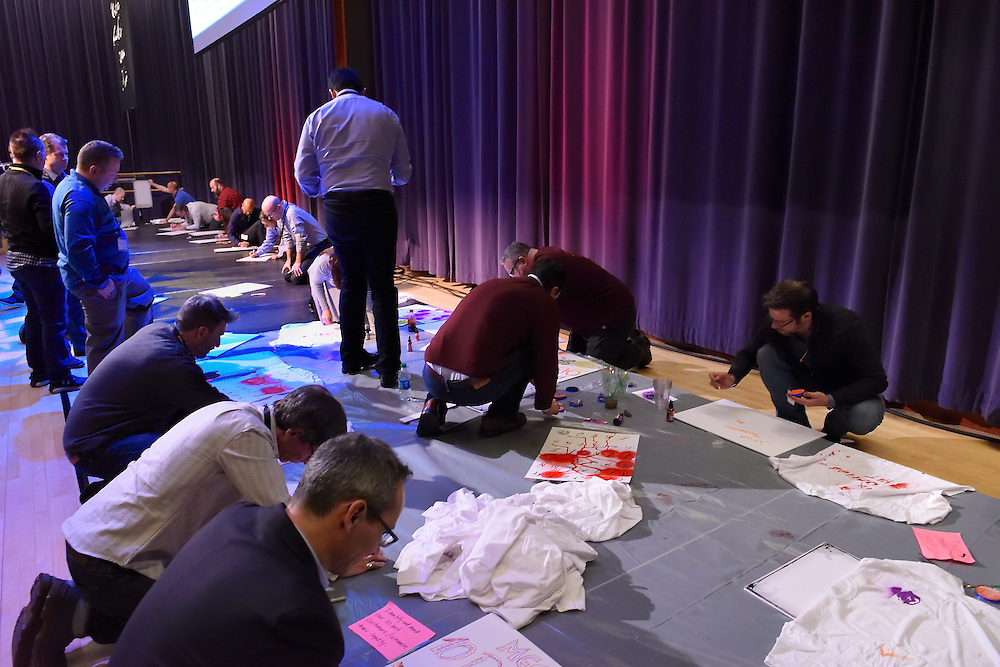 Team members spread out on the floor creating artwork for their signage.