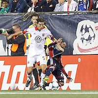 New England Revolution midfielder Lee Nguyen (24) tackles D.C. United defender Dejan Jakovic (5). In a Major League Soccer (MLS) match, the New England Revolution (blue) defeated D.C. United (white), 2-1, at Gillette Stadium on September 21, 2013.