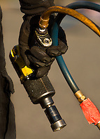 Detail photo of hand holding NASCAR tool during a pit stop training activity.