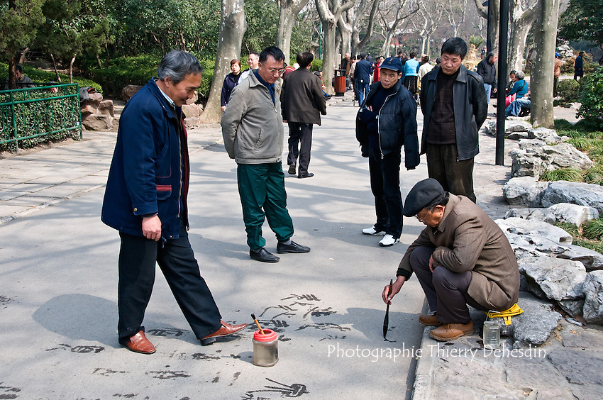 Asia, China, Shanghai (March 2008).People practicing Chinese Shufa with a brush and water on a path in Luxun Park..Chinese Shufa is Chinese calligrafic handwriting. Calligraphy in China is an Art hold in equal importance as painting.