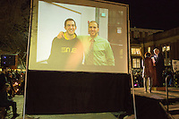 UNC Chancellor Carol Folt and NC State Chancellor Randy Woodson on stage by a projected image of Deah Barakat (left) and an unknown friend, as thousands gathered for a vigil and memorial for three shooting victims at The Pit at The University of North Carolina at Chapel Hill in Chapel Hill, North Carolina on Wednesday, February 11, 2015. Craig Hicks, 46, of Chapel Hill has been charged with three counts of first-degree murder in the killings of Deah Barakat, 23, a UNC student; his wife, Yusor Abu-Salha, 21; and her sister, Razan Abu-Salha, 19. (Justin Cook)
