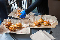 Bareburger Organic serves sliders after the unveiling of the new wayfinding kiosks that stand at either end of Restaurant Row in New York, West 46th street between 8th and 9th Avenues, on Tuesday May 16, 2017. At least four years in the making the illuminated kiosks show the names of the many eateries that populate the street. The unveiling is just in time for the Taste of Times Square event taking place on the street on June 5. (© Richard B. Levine)