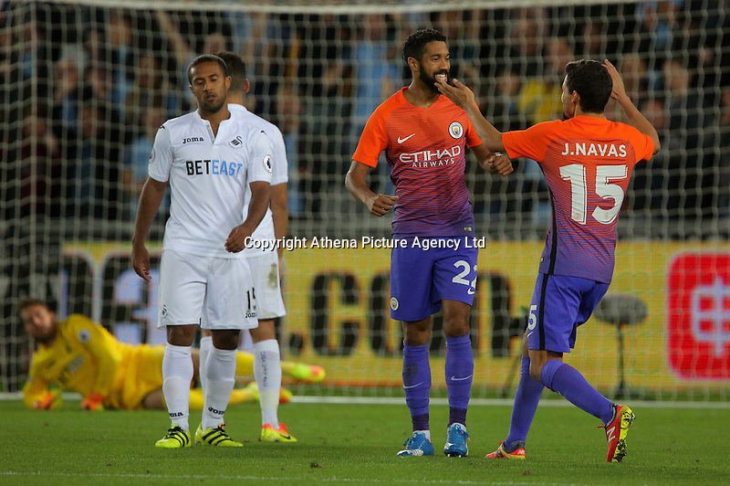 Dael Clichy of Manchester City (C) celebrates his opening goal with team mate Jesus Navas (R) next to disappointed Wayne Routledge (L) during the EFL Cup Third Round match between Swansea City and Manchester City at The Liberty Stadium in Swansea, Wales, UK. Wednesday 21 September.